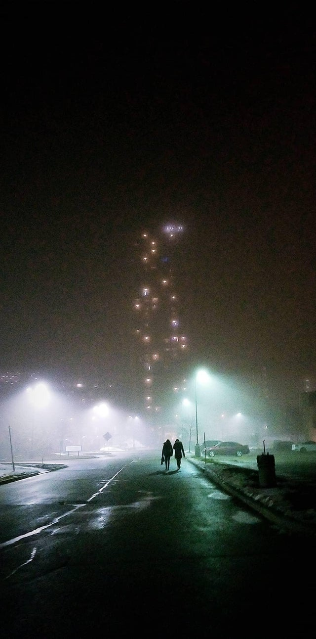 Two people under a blue streetlight on a foggy night