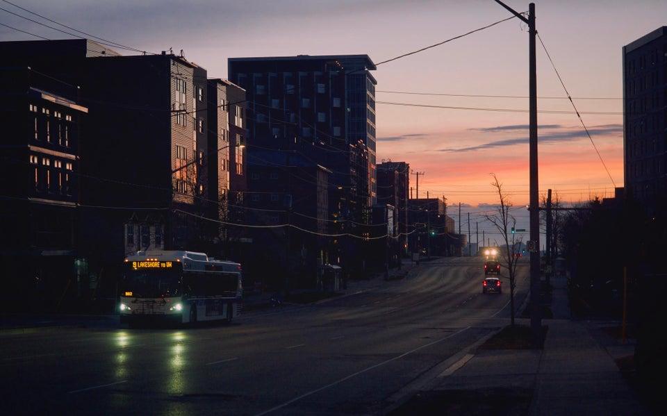 pink sky, empty street, a single bright bus
