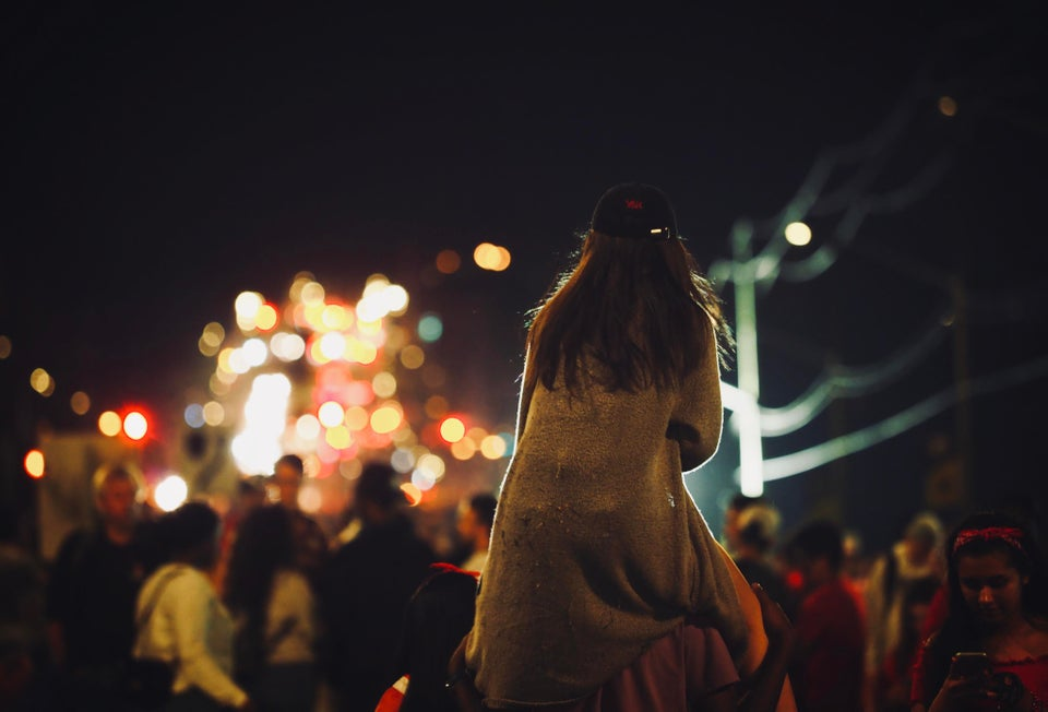 A person on their friend's shoulders beholding Canda Day's bright lights and fireworks